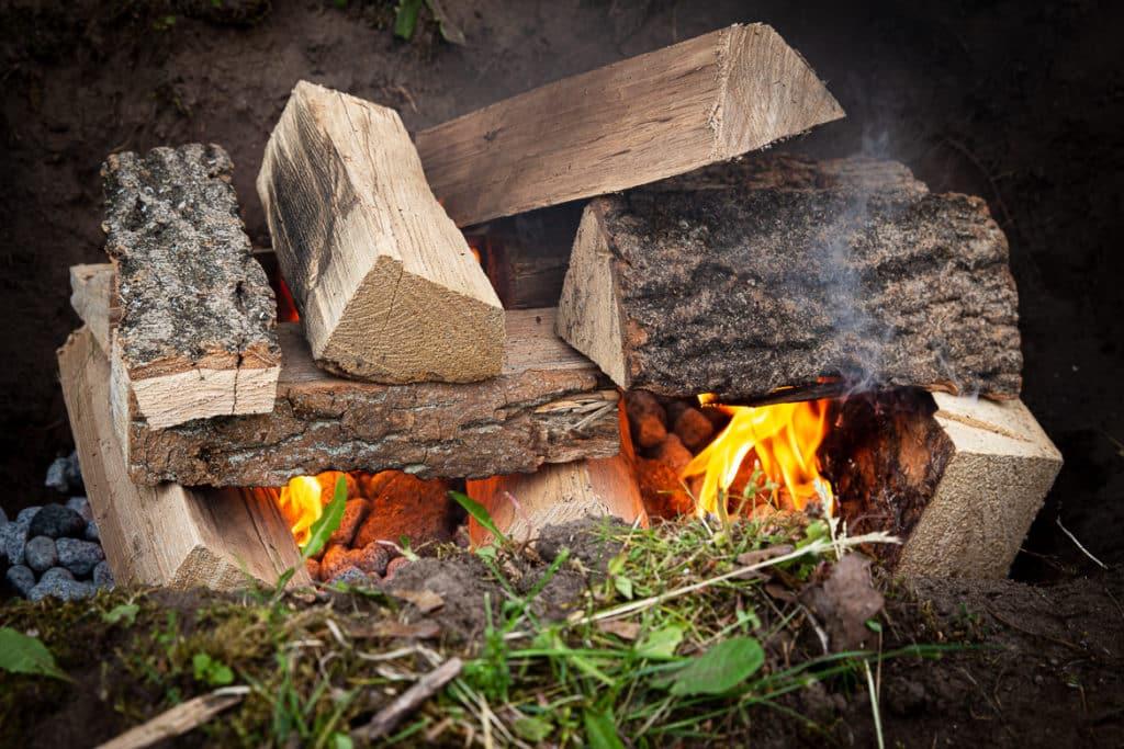 Holzscheite im Erdloch anzünden