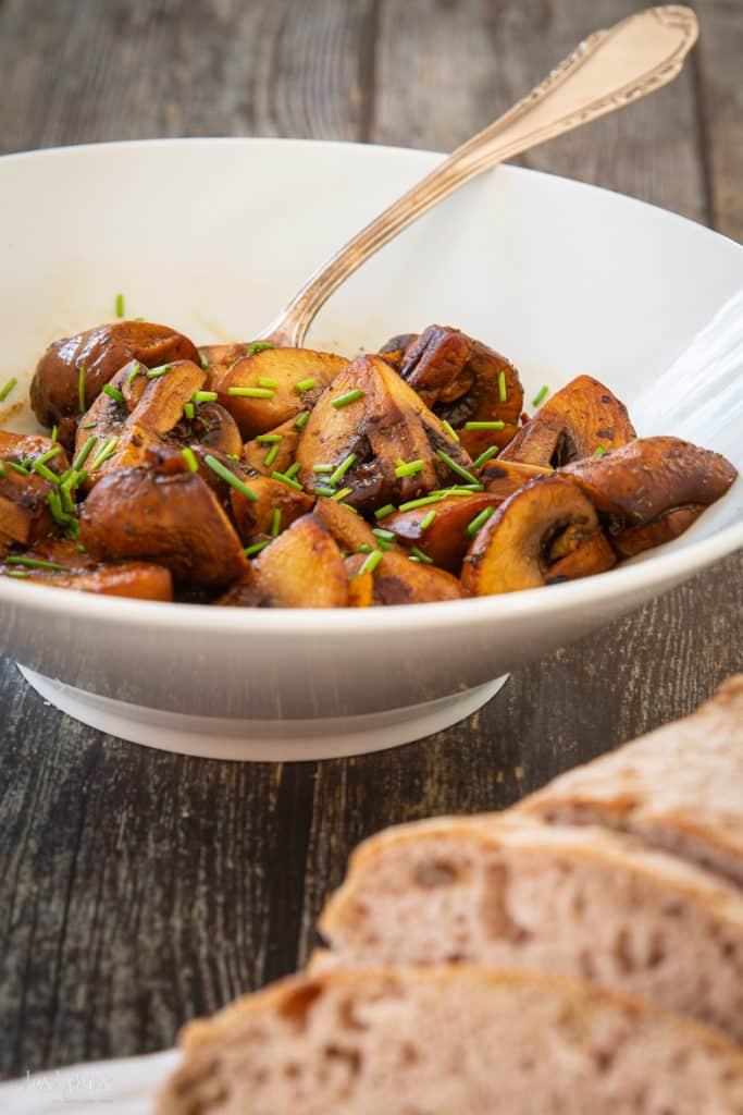 Balsamico-Champignons auf Teller mit Brot davor