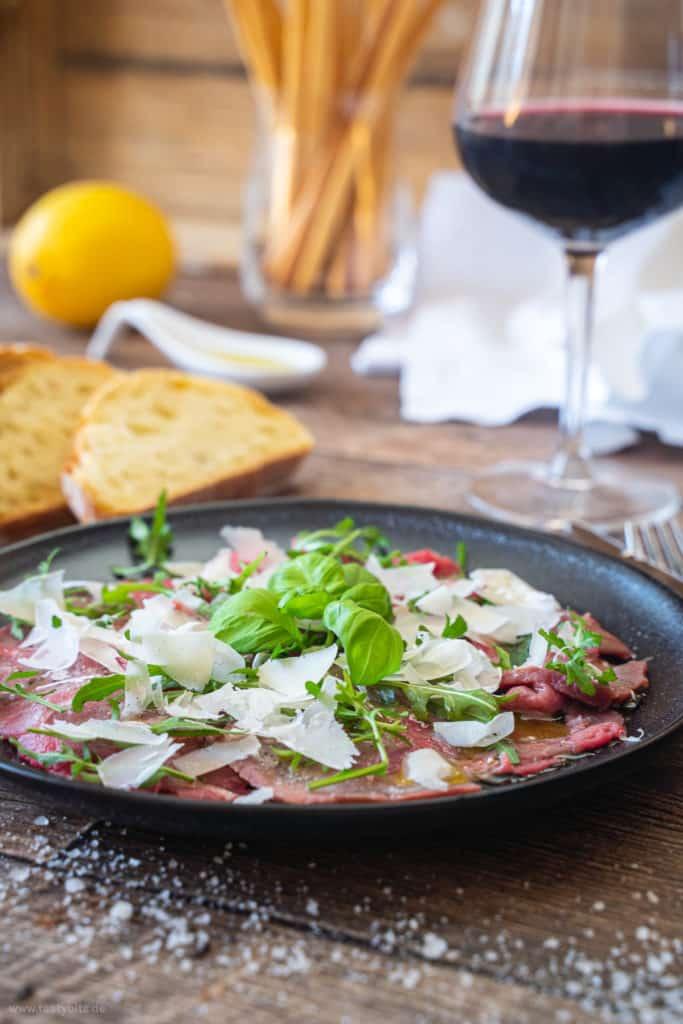 Italienisches Carpaccio mit einem Glas Rotwein im Hintergrund
